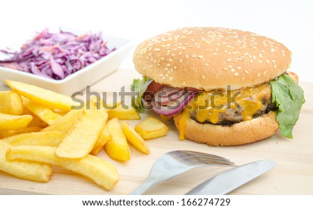 A big cheeseburger with french fried potatoes and cabbage on a wood cutting board - stock photo