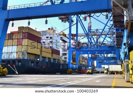 A big container vessel in a container seaport during transportation of cargo in containers by cranes and lorry trucks. - stock photo