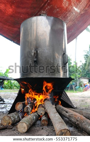 a big cylinder or black pot boiling water for cooking on the fired stove next to firewood pile, a Malaysian or Asian traditional culture ancient method to cook rice