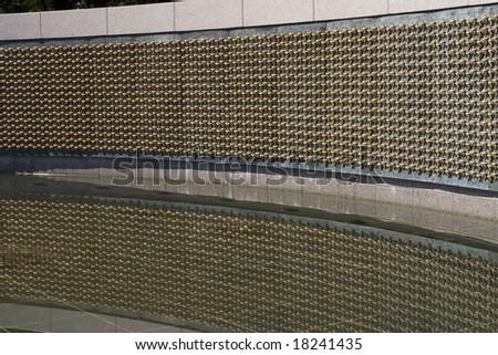 A big display of gold stars on the WWII memorial in Washington DC. Each star represents 100 American deaths. With reflection in water - stock photo