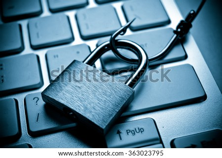 A big fish hook with security lock on computer keyboard - Computer data theft concept / phishing - stock photo