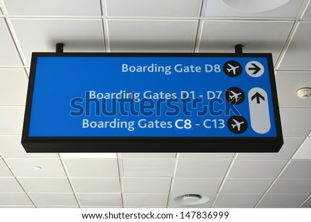 A big illuminated black and blue airport sign showing direction to the different boarding gates at the airport.