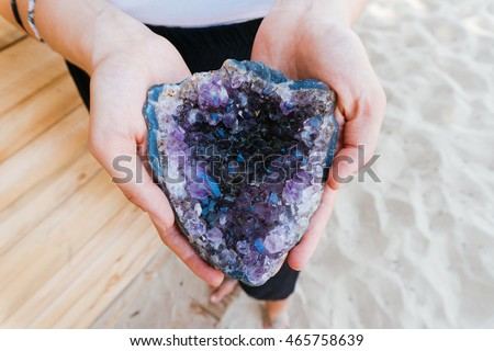 A big piece of amethyst in the hands of a woman, rare, magic stone talisman in the hands