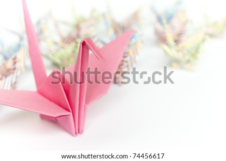 A big pink paper bird and a group of small paper birds, shallow depth of field - stock photo