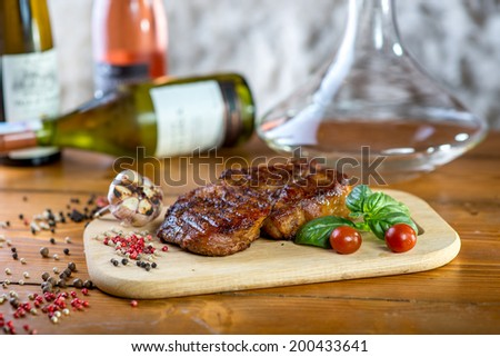 A big pork steak with spices, tomatoes and bottles of wine on the background - stock photo
