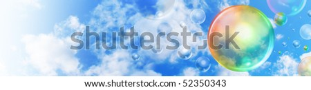 A big rainbow colored bubble is floating in the sky with smaller bubbles in the background. There are clouds and copyspace area for your text as a header graphic. - stock photo