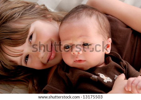 A big sister holding her baby brother - stock photo