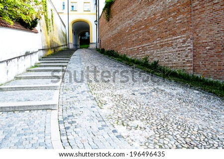 A big stairway of stones along a big brown wall. - stock photo