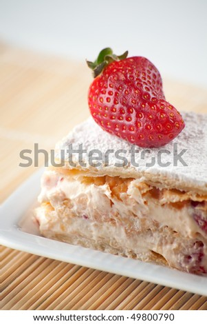A big strawberry Millefuille with lemon custard and icing sugar on top with fresh strawberries. Shallow depth of Field on strawberry - stock photo