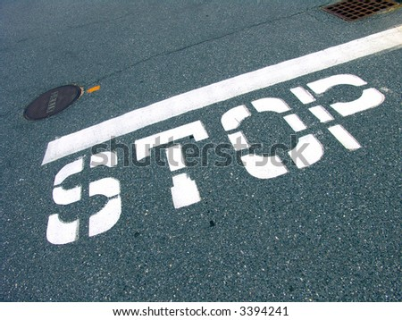 A big traffic stop sign painted on the road surface