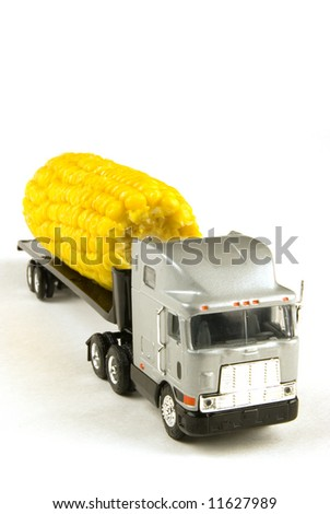 a big truck moving some corn on white
