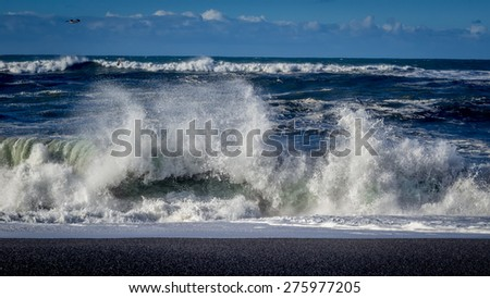 A big wave crashes on the beach.