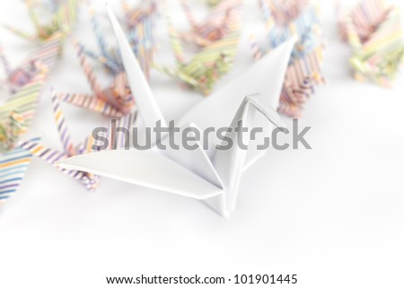A big white paper bird and a group of small paper birds, shallow depth of field - stock photo