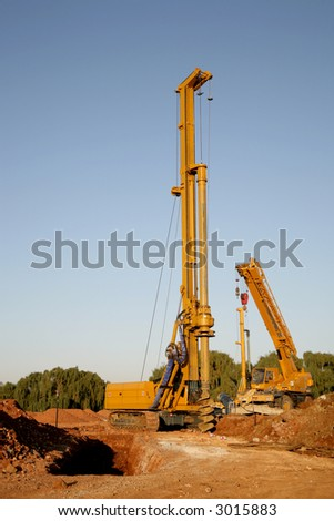 A big yellow drill digging holes in the ground - stock photo