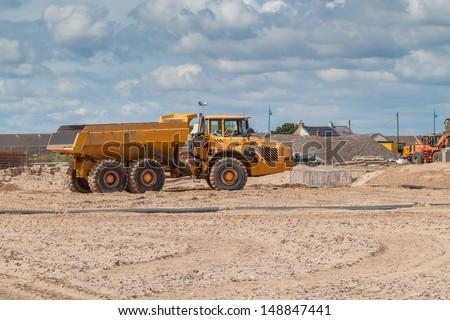 A Big Yellow Dump Truck on a Beach Construction Site - stock photo