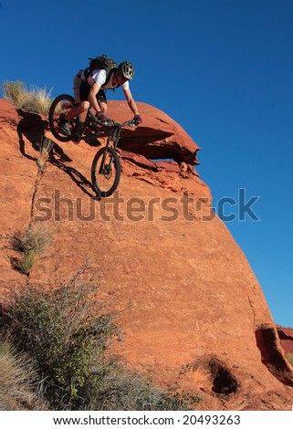 A biker drops down a steep sandstone face.