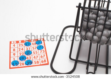 A bingo cage, balls with numbers, card and markers. - stock photo