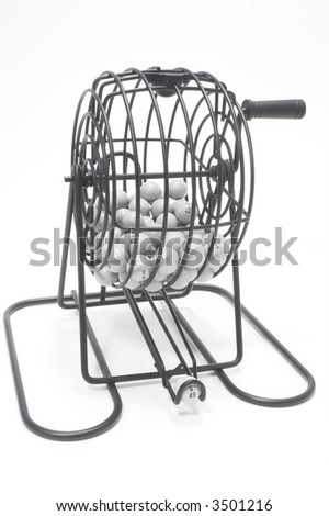 A bingo game cage with numbered balls. - stock photo