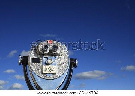 A binocular viewer looking out over blue sky. - stock photo