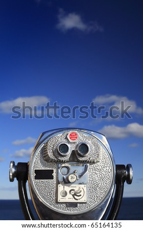 A binocular viewer looking out over water and blue sky. - stock photo