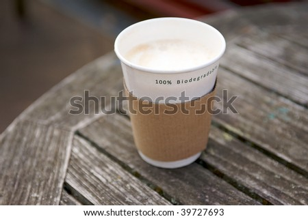 A Biodegradable Disposable Cup containing a hot drink on a wooden table surface in shallow DOF - stock photo