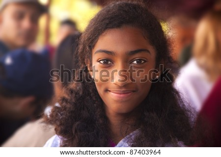 A biracial girl smiling in the crowd. - stock photo