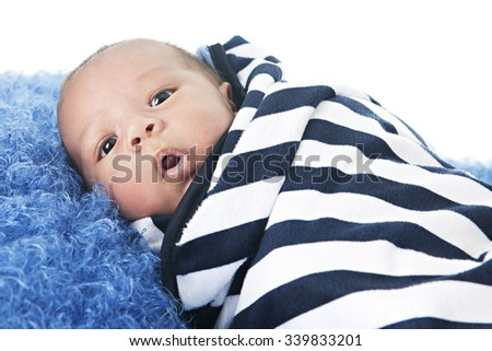 A biracial newborn swaddled in a black and white striped blanket.  On a white background.