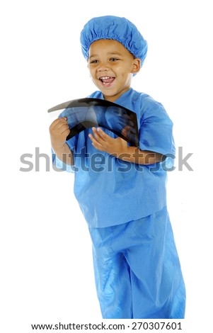 "A biracial preschool ""surgeon"" delighted with the x-ray of a hand that he holds.  On a white background."