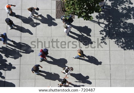 A bird's eye view of a crowd of people strolling down a sidewalk. - stock photo