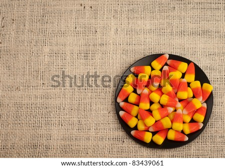 A Bird's Eye View of Candy Corn in a Dish for Halloween or Thanksgiving Themed Invitation or Card with Area for Your Words - stock photo