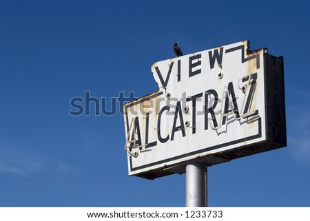 "A bird sits atop a broken old sea-side neon sign that reads ""View Alcatraz�."
