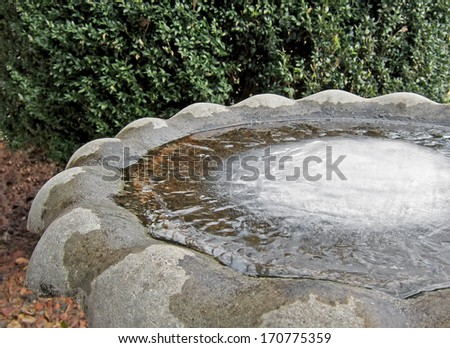 A birdbath completely frozen on a Winter day. - stock photo