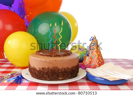 A birthday cake and balloons with whitespace for copy - stock photo