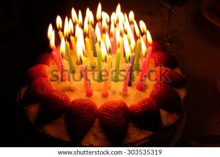 a birthday strawberry cake with lighted candles - stock photo