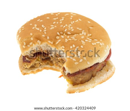 A bitten veggie burger on a bun with ketchup isolated on a white background.