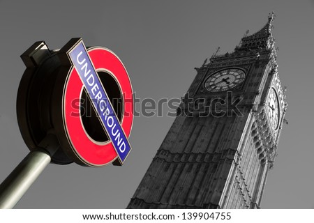 A black a white image of the place of Westminster with a color image of the underground sign in the foreground - stock photo