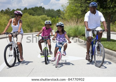 A Black African American family of two parents and two children, two girls, cycling together. - stock photo