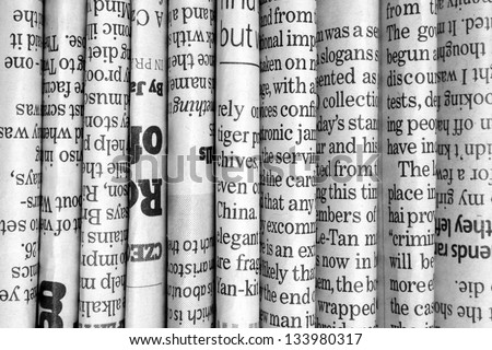 A Black And White Background Of English Language Newspapers Stacked Folded In Vertical Position