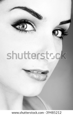 A black and white close up of a beautiful smiling young woman in front of a white background. Studio/Beauty shot.