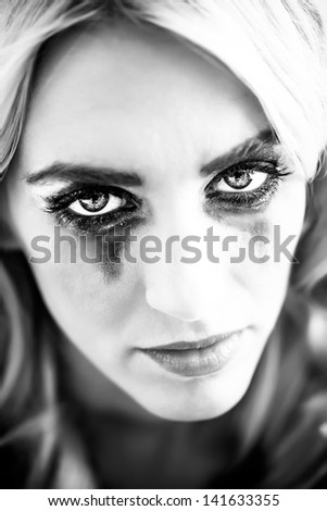a black and white close-up portrait of a beautiful blond caucasian model with black make-up smudged down her teary cheeks - stock photo