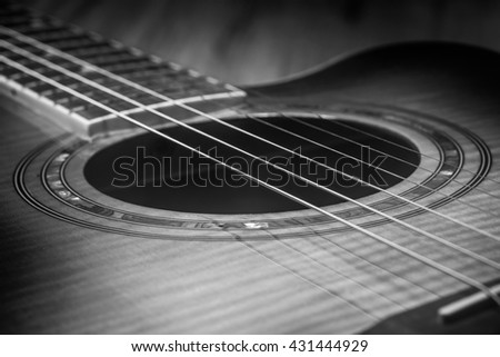 A black and white closeup of the strings and sound hole of an acoustic guitar.