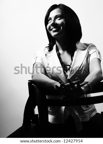 A black and white high-key portrait about a pretty trendy lady with black hair who is sitting on a chair, she is looking up and she is smiling. She is wearing a white coat and a stylish necklace. - stock photo