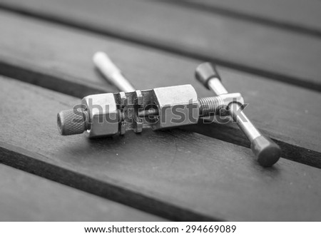 A black and white image of a bicycle chain splitter tool - stock photo