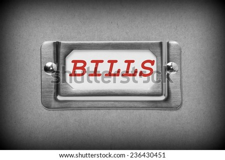 A black and white image of a metal drawer label holder with a white card and the title Bills added in red text - stock photo