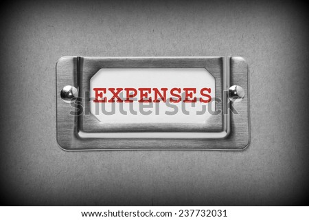 A black and white image of a metal drawer label holder with a white card and the title Expenses added in red text - stock photo
