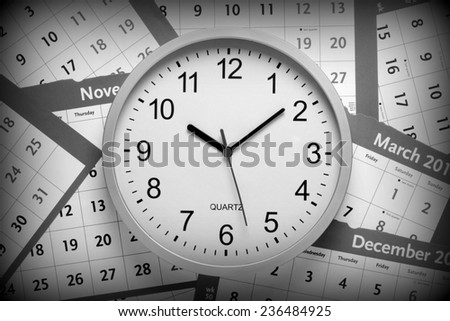 A black and white image of a modern office clock on a background of pages torn from a  wall calendar. A vignette has been added for effect. - stock photo
