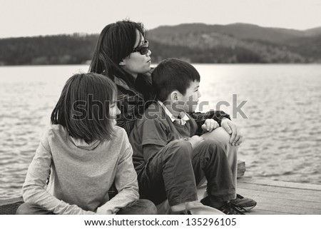 A black and white image of a mother and her two kids looking out into Hauser Lake in Idaho. - stock photo