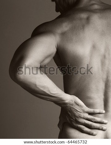 A black and white image of a muscular man holding his lower back as if experiencing a backache. - stock photo