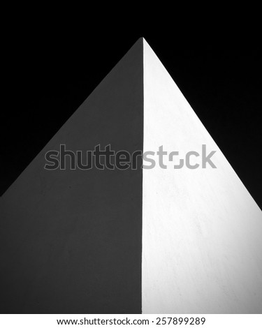 A black and white image of a pyramid. - stock photo
