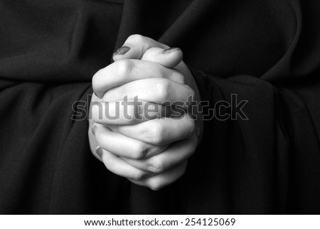 A black and white image of a womans hands clasped in prayer. - stock photo